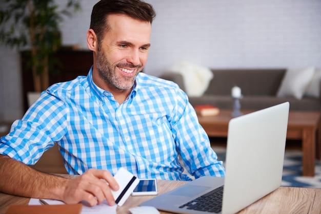 Gelukkige man die laptop en creditcard gebruikt tijdens online winkelen