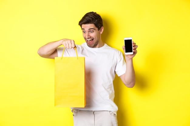Gelukkige man die naar boodschappentas kijkt en het scherm van de mobiele telefoon toont. concept van online bankieren en geld