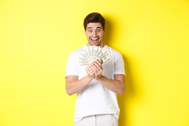 Gelukkige man die naar geld kijkt en opgewonden glimlacht, prijs wint, banklening krijgt, over gele achtergrond staat