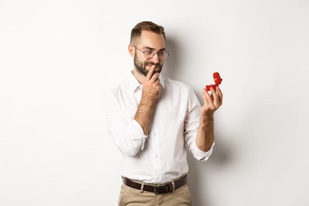 Gelukkige man die nadenkend naar trouwring in doos kijkt, nadenkend over huwelijksaanzoek