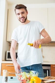 Gelukkige man die olijfolie in salade toevoegt in de keuken en naar voren kijkt