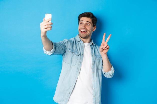 Gelukkige man die selfie neemt en vredesteken toont op blauwe achtergrond, met mobiele telefoon