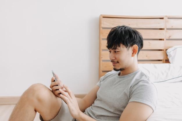 Gelukkige man die smartphone gebruikt terwijl hij ontspant in zijn appartement, blijf thuis