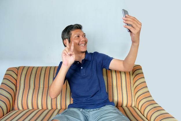 Gelukkige man die videogesprek voert met de telefoon thuis