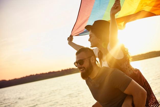 Gelukkige man die vrouw met regenboogvlag over zee draagt