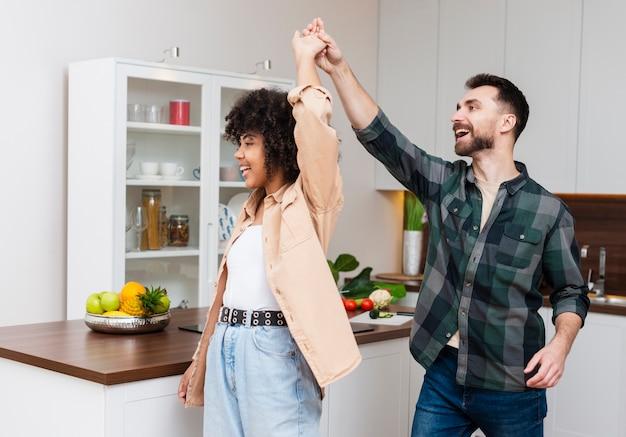 Gelukkige man en vrouw die in keuken dansen