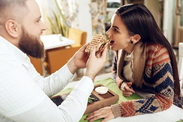 Gelukkige man en vrouw die lunch in een restaurant hebben
