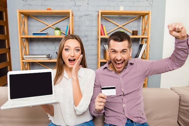 Gelukkige man en vrouw die met laptop en bankkaart gillen