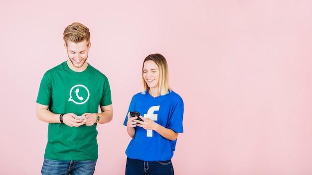 Gelukkige man en vrouw die smartphone op roze achtergrond gebruiken
