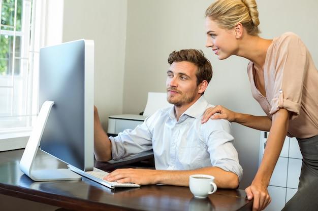 Gelukkige man en vrouw die terwijl het werken aan computer op kantoor bespreken