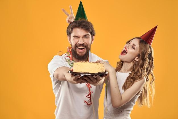 Gelukkige man en vrouw in een pet die een verjaardag vieren met een cake in hun handen