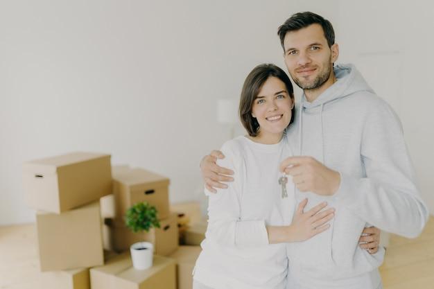 Gelukkige man en vrouw kopen onroerend goed, knuffelen en houden sleutels vast, staan in woonkamer met dozen in nieuw huis