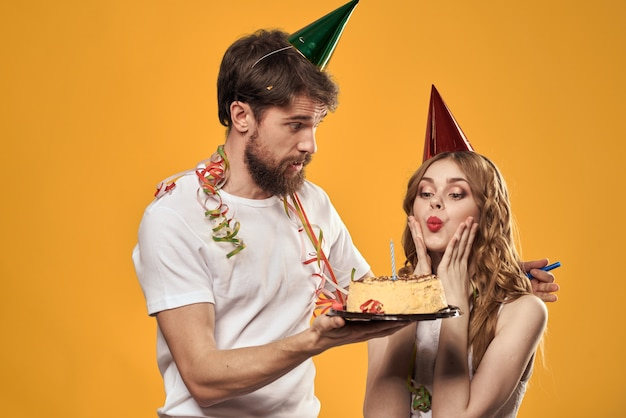 Gelukkige man en vrouw met de verjaardagspartij van de verjaardagstaart en gele achtergrond