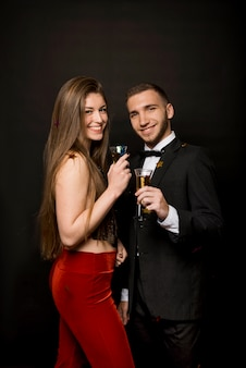 Gelukkige man en vrouw met glazen drankjes en confetti