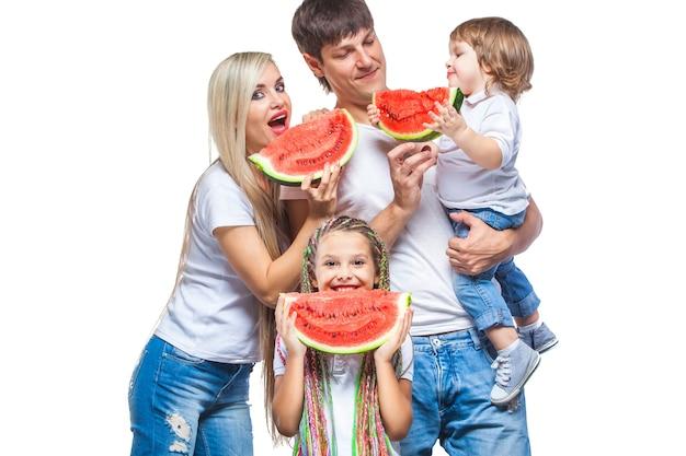 Gelukkige man en vrouw met twee kinderen die watermeloen gaan eten die op wit wordt geïsoleerd