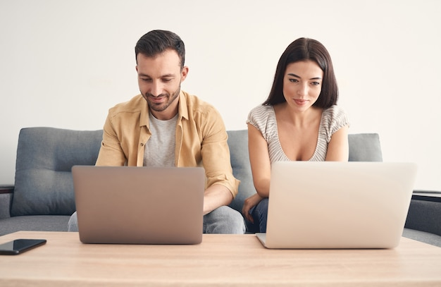 Gelukkige man en vrouw zitten samen op de bank terwijl ze aandachtig op hun computers in de kamer werken