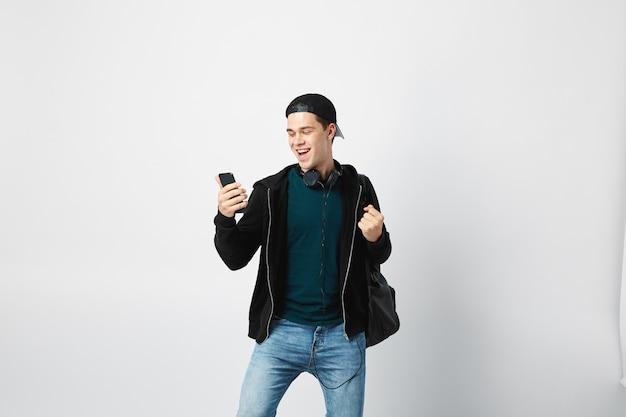 Gelukkige man gebruikt mobiele telefoon in de studio op een witte achtergrond