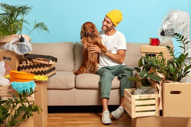 Gelukkige man huisdieren rashond, poseren op de bank, verhuizen naar een nieuw huis, veel kartonnen dozen in de buurt, verheugd over het kopen van een moderne flat, rust uit na het intrekken.