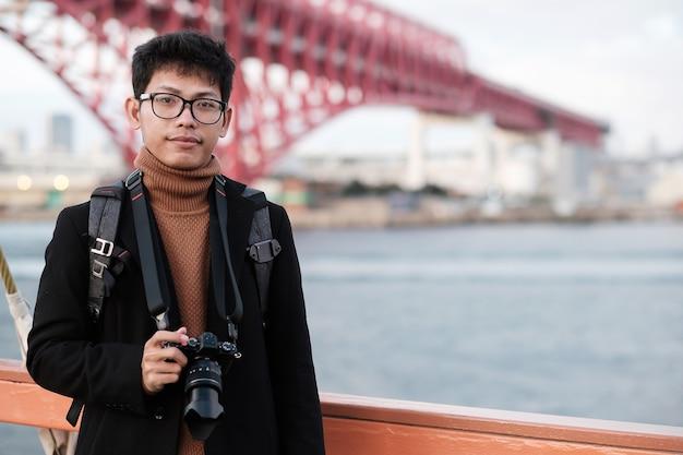 Gelukkige man in jas en camera, aziatische reiziger geniet van en uitzicht op de bezienswaardigheden in het schip
