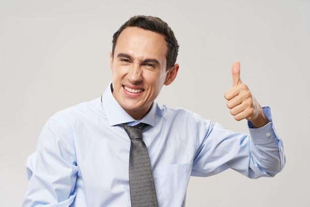 Gelukkige man in overhemd en stropdas toont positief gebaar en glimlacht