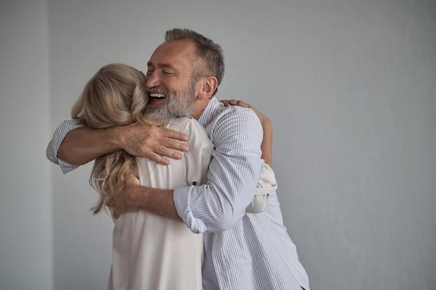 Gelukkige man knuffelt zijn vrouw na hun reünie