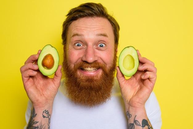 Gelukkige man met baard en tatoeages houdt een avocado vast