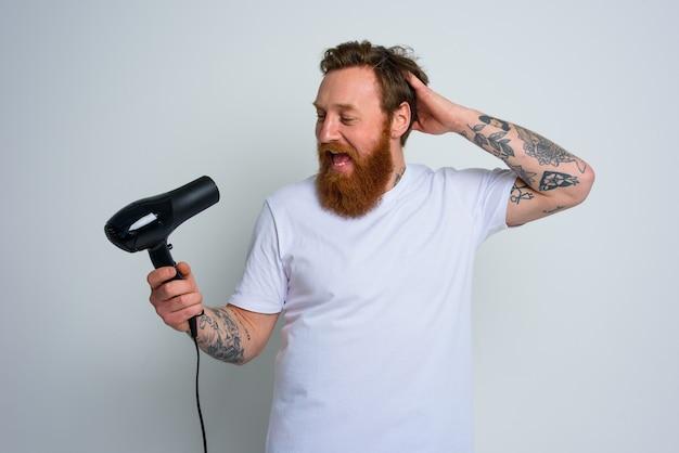 Gelukkige man met baard gebruikt föhn als microfoon en danst