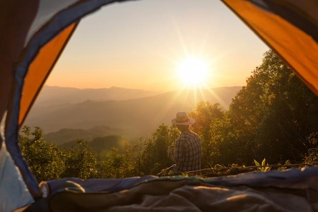Gelukkige man met bedrijf koffiekopje verblijf in de buurt van tent rond de bergen