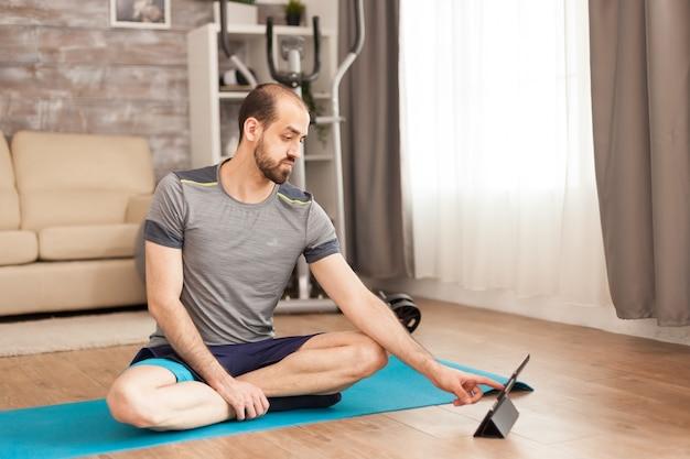 Gelukkige man met een gezonde levensstijl die naar yogales kijkt op tabletcomputer tijdens covid-19 zelfisolatie.