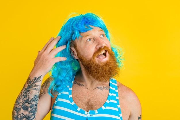 Gelukkige man met reddingsboei, zwempak en blauwe pruik gedraagt zich als een gelukkige vrouw