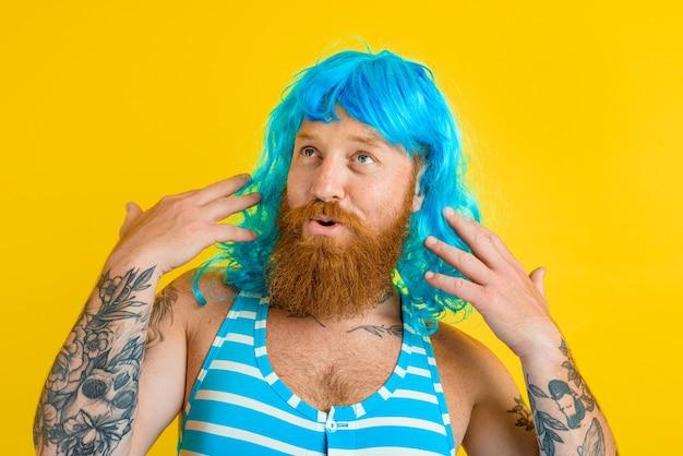 Gelukkige man met zwempak met reddingsboei en blauwe pruik gedraagt zich als een gelukkige vrouw