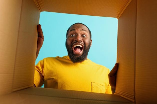 Gelukkige man ontvangt een pakket van een online winkelbestelling. blije en verbaasde uitdrukking. cyaan muur.