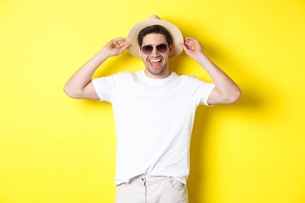 Gelukkige man op vakantie, met strohoed en zonnebril, glimlachend terwijl hij tegen een gele achtergrond staat.