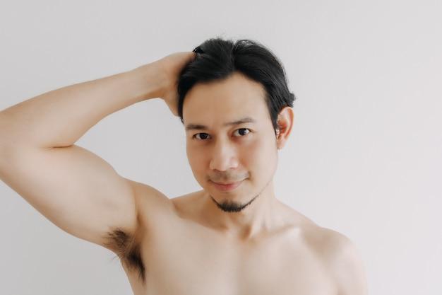 Gelukkige man pronkt met zijn gezicht en brengt huidverzorgingsproduct aan