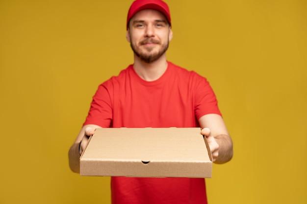 Gelukkige man van bezorgservice in rood t-shirt en pet die voedselbestelling geeft en pizzadoos houdt die over gele muur wordt geïsoleerd