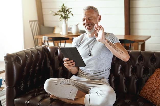 Gelukkige man van middelbare leeftijd in vrijetijdskleding die naar iemand zwaait terwijl hij een digitaal videogesprek voert