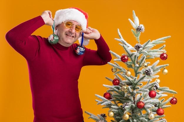 Gelukkige man van middelbare leeftijd met kerstkerstmuts in donkerrode coltrui en gele bril met kerstballen op zijn oren die naast een kerstboom over oranje muur staan