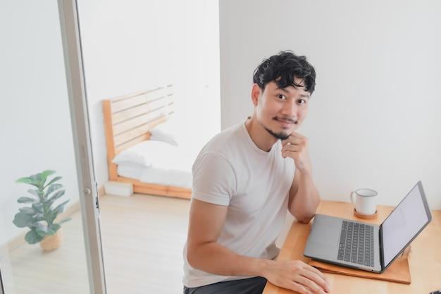 Gelukkige man werkt in zijn appartementconcept van thuiswerken
