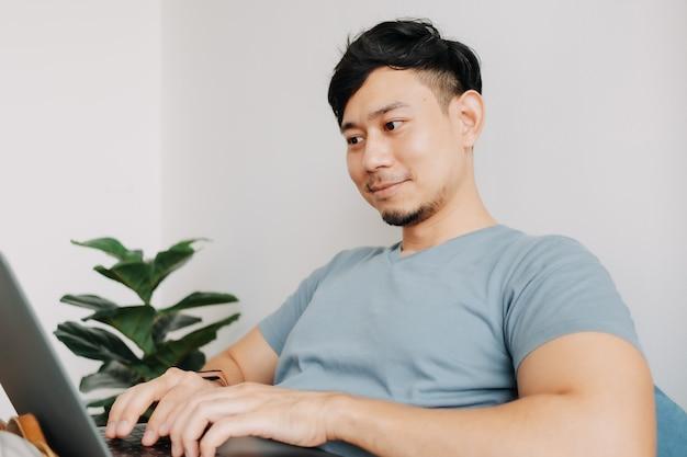 Gelukkige man werkt met computerlaptop terwijl hij thuis blijft werken thuis