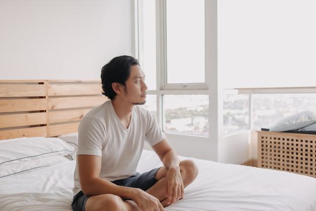 Gelukkige man zit en ontspant op zijn bed in zijn appartement