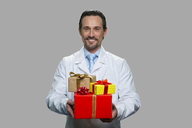 Gelukkige mannelijke arts die vele giftdozen houdt. knappe man in wit uniform geschenkdozen aanbieden. fijne wintervakantie.