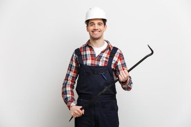 Gelukkige mannelijke bouwer in de beschermende koevoet van de helmholding over grijze muur