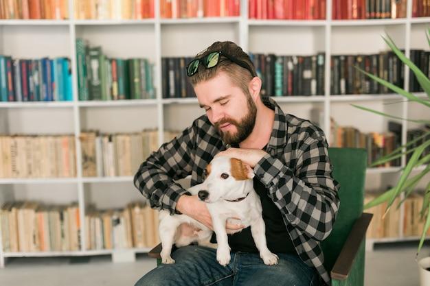 Gelukkige mannelijke eigenaar van jack russell terrier-hond, voelt zich verantwoordelijk voor het geven van huisdieren, staande tegen de achtergrond van boekenplanken. mensen en relatie met dieren