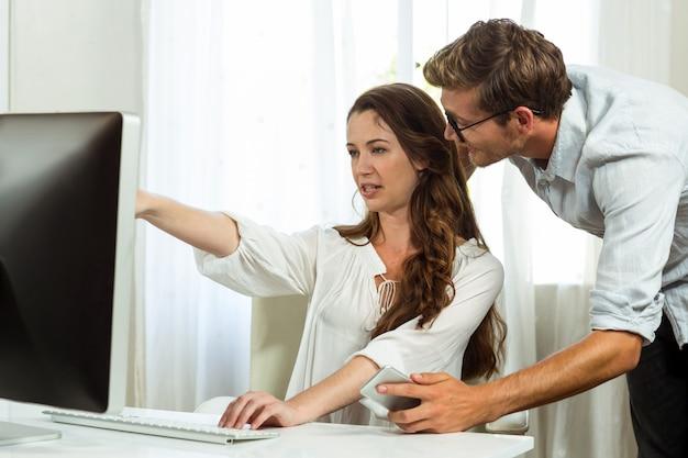 Gelukkige mannelijke en vrouwelijke collega's die computer met behulp van op kantoor