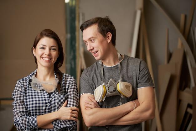 Gelukkige mannelijke en vrouwelijke schrijnwerkers met gekruiste armen in werkplaats