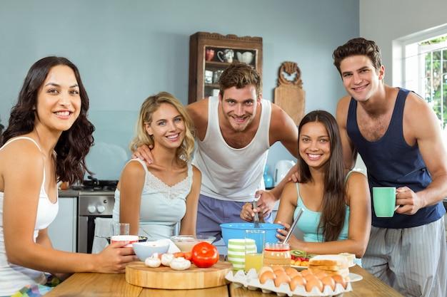 Gelukkige mannelijke en vrouwelijke vrienden die in keuken bij huis koken