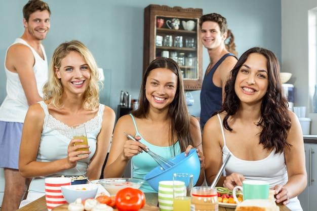 Gelukkige mannelijke en vrouwelijke vrienden die samen in keuken koken