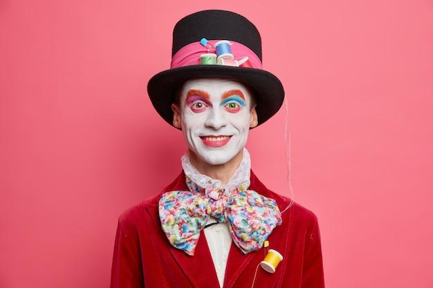 Gelukkige mannelijke hoedenmaker met kleurrijke make-upjurken voor halloween-feest heeft een afbeelding van een fictief personage uit wonderland poseert tegen een levendige roze studiomuur