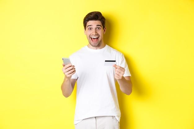 Gelukkige mannelijke koper met smartphone en creditcard, concept van online winkelen op internet, staande op gele achtergrond.