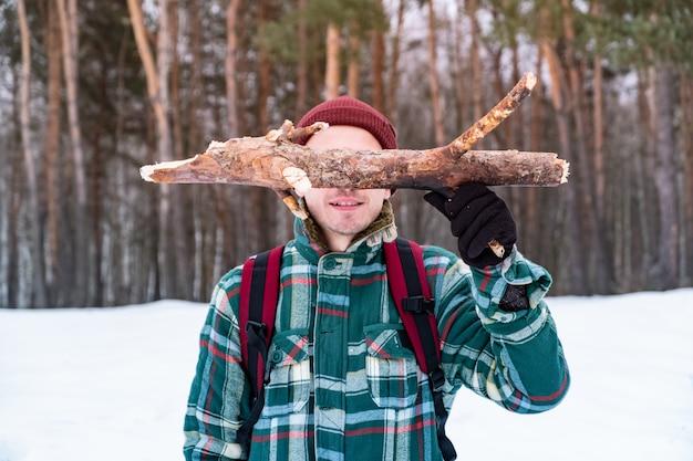 Gelukkige mannelijke persoon die in de winterbos wandelt. de glimlachende mens in geruit de winteroverhemd houdt een logboek van pijnboomhout